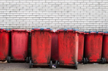 many red dirty garbage bins against a gray brick wall (copy-space available)