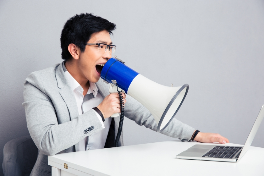 Businessman screaming in megaphone on laptop